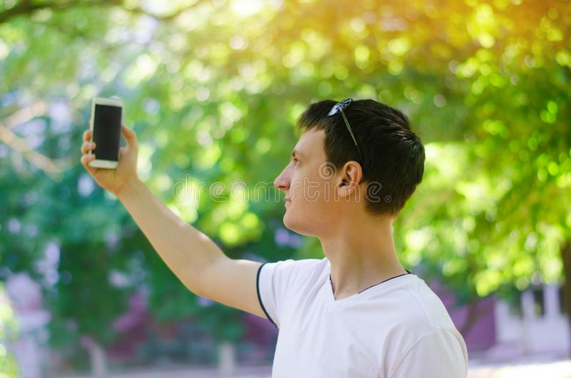Beautiful young European guy taking pictures of himself and makes selfie in a city park outdoors. lifestyle, concept walks. royalty free stock photos