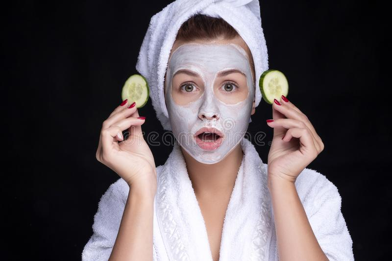Beautiful young european woman apply clay mask on her face with towel on her head and cucumbers on her eyes. beauty spa concept stock images