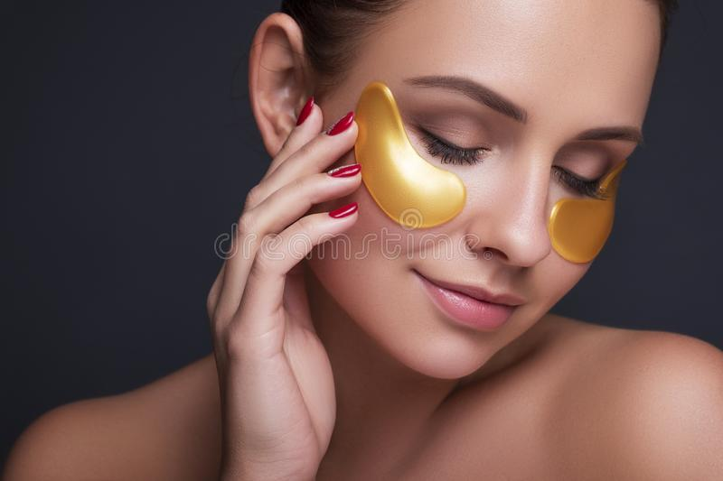 Beautiful young european woman apply clay mask on her face with towel on her head and cucumbers on her eyes. beauty spa concept royalty free stock photography
