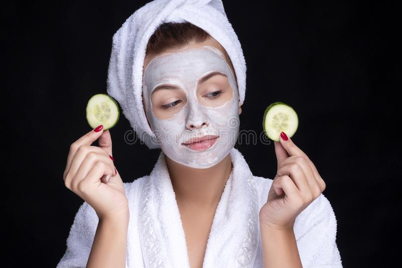 Beautiful young european woman apply clay mask on her face with towel on her head and cucumbers on her eyes. beauty spa concept royalty free stock image