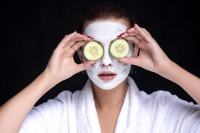 Beautiful young european woman apply clay mask on her face with towel on her head and cucumbers on her eyes. beauty spa concept royalty free stock photo