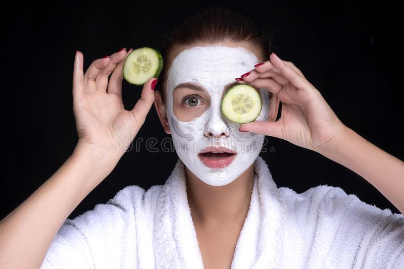 Beautiful young european woman apply clay mask on her face with towel on her head and cucumbers on her eyes. beauty spa concept royalty free stock photos