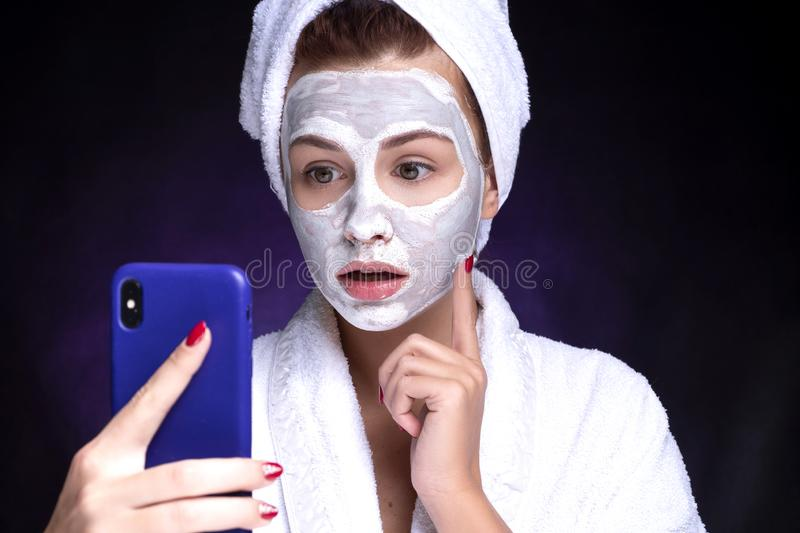 Beautiful young european woman apply clay mask on her face with towel on her head. She make selfie. Beauty spa concept stock image
