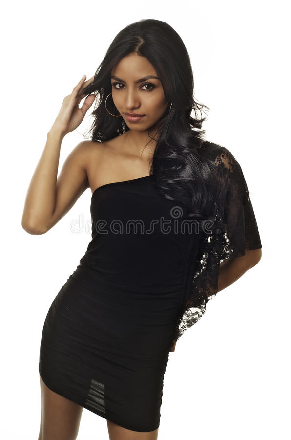 Beautiful young exotic woman. Wearing black dress isolated against dark background royalty free stock photos