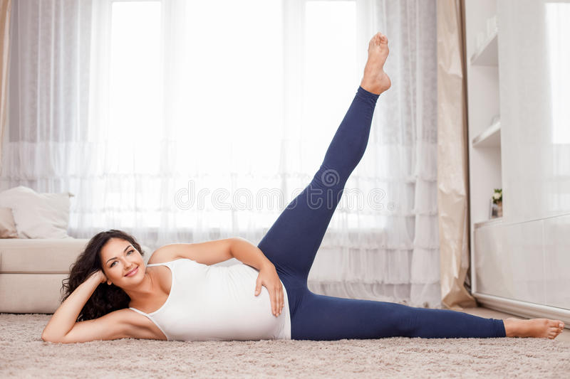 Beautiful young expectant mother is exercising stock images