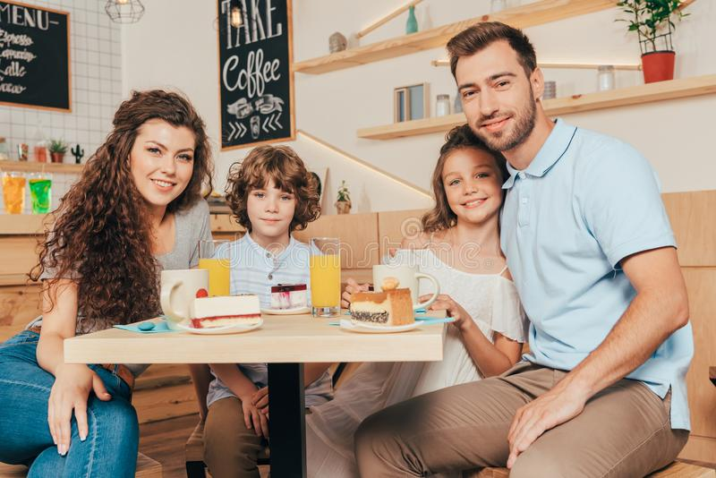 Beautiful young family eating cakes. In modern cafe royalty free stock images