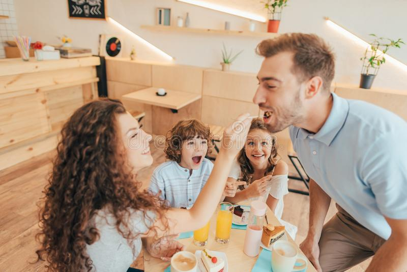 Beautiful young family eating sweets in cafe with modern. Trendy interior stock photo