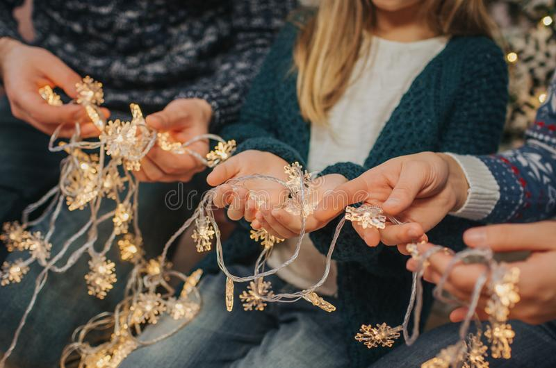 Beautiful young family enjoying their holiday time together, decorating Christmas tree, arranging the christmas lights royalty free stock photo