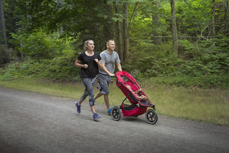 Couple exercising and jogging together pushing their baby in a stroller royalty free stock photo