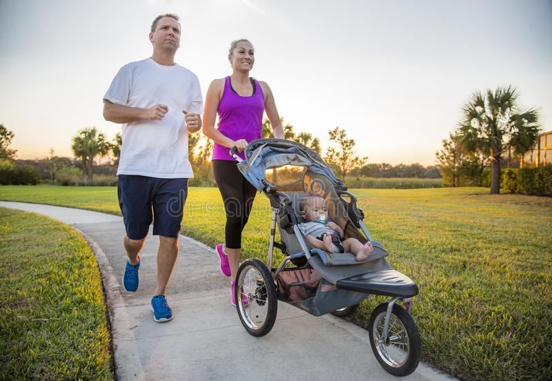 Couple exercising and jogging together at the park pushing their baby in a stroller royalty free stock image