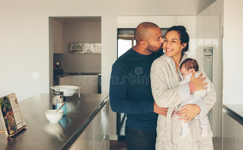 Beautiful young family in kitchen stock photography