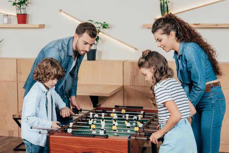 Beautiful young family family playing table football. In cafe royalty free stock photo