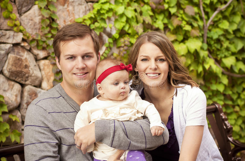 Beautiful Young Family Portrait. A portrait of a beautiful young family with their cute new baby girl stock image