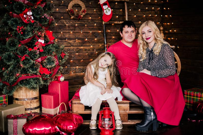 Beautiful young family in red having fun together for Christmas holidays, sitting on a living room floor next to a nicely decorate royalty free stock images