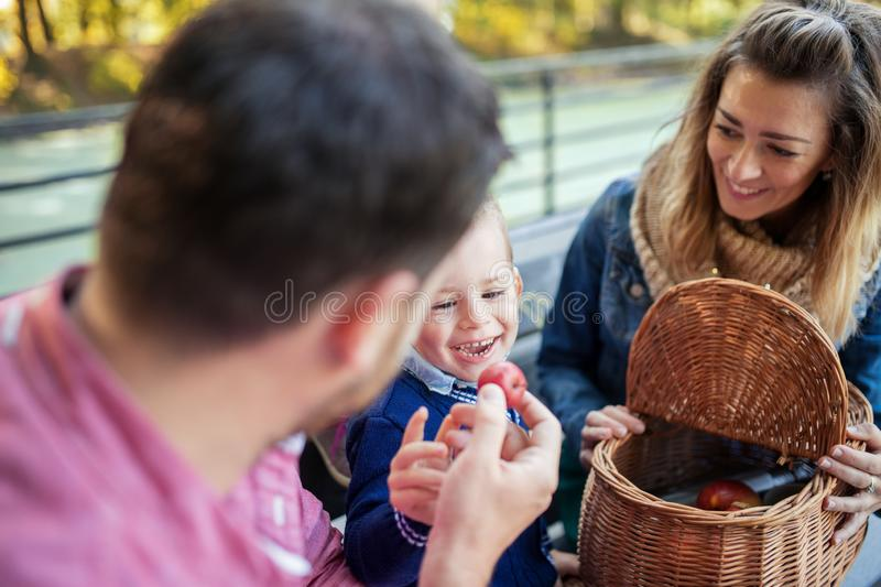 Beautiful young family with small son sitting on bench in autumn park. stock photography
