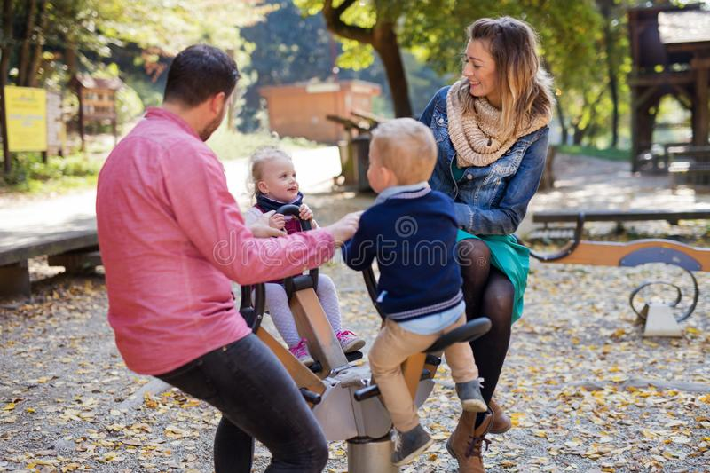 Beautiful young family with small twins playing on playground in autumn. stock photo