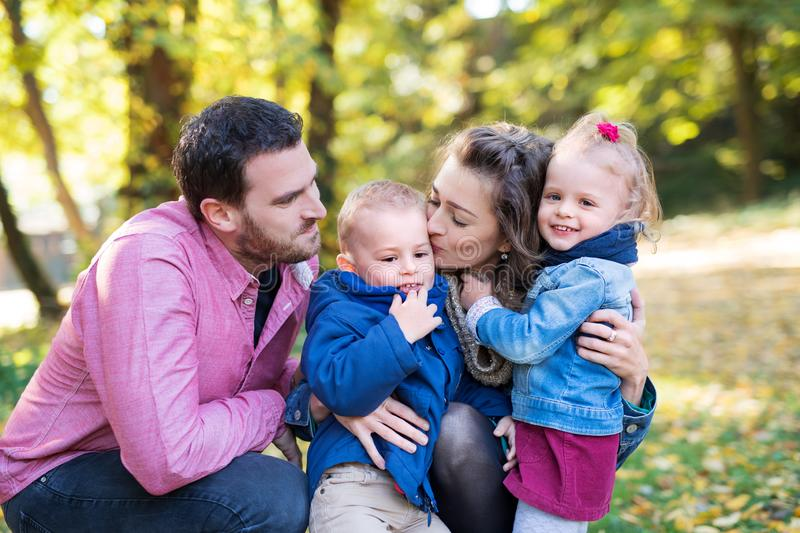 Beautiful young family with small twins on a walk in autumn forest, kissing. stock images