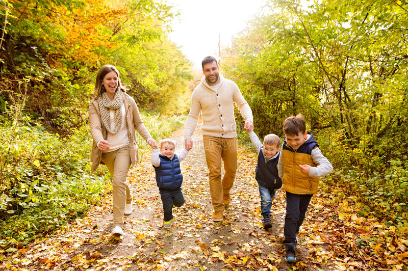 Beautiful young family on a walk in autumn forest. royalty free stock photo
