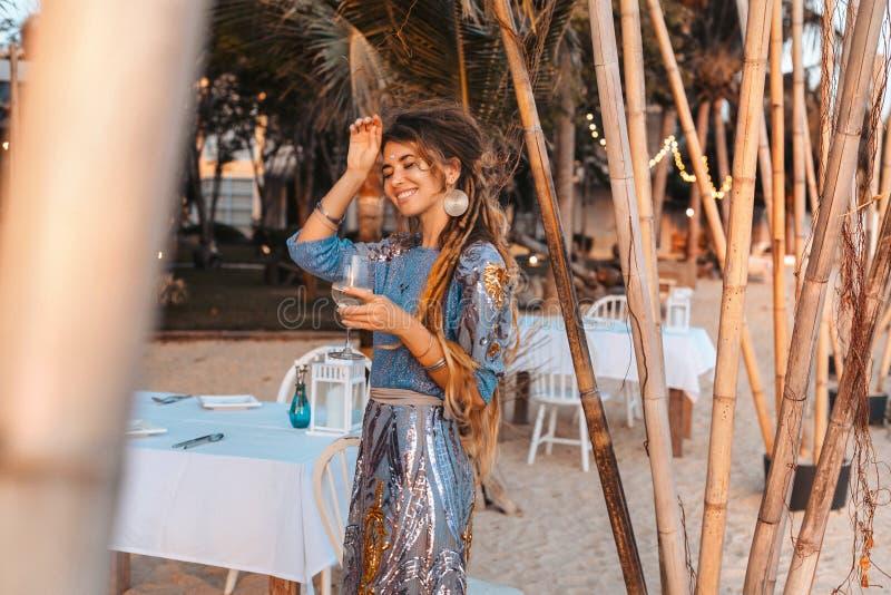 Beautiful young fashion model in elegant dress at sunset at resort stock image