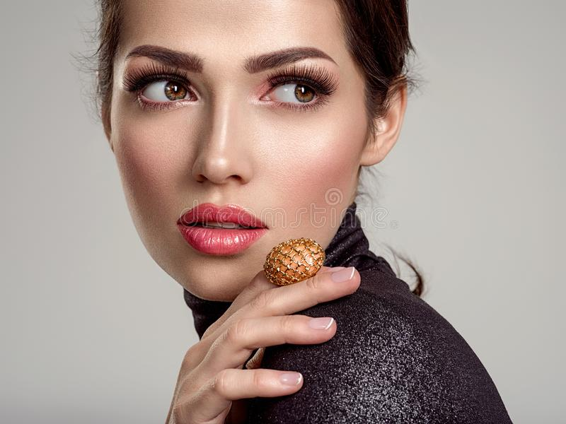 Beautiful young fashion woman with living coral lipstick. Attractive white girl wears luxury jewelry royalty free stock images