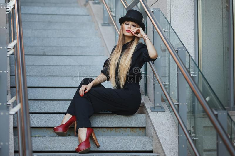 Beautiful young fashionable woman posing in black suite, red shoes with high heels and black hat. Vogue style. Urban background royalty free stock photography