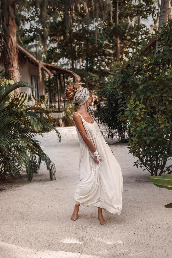 Beautiful young fashionable woman in turban at natural tropical background stock image