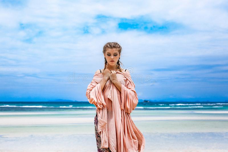 Beautiful young fashionable woman walking by the shore line royalty free stock image