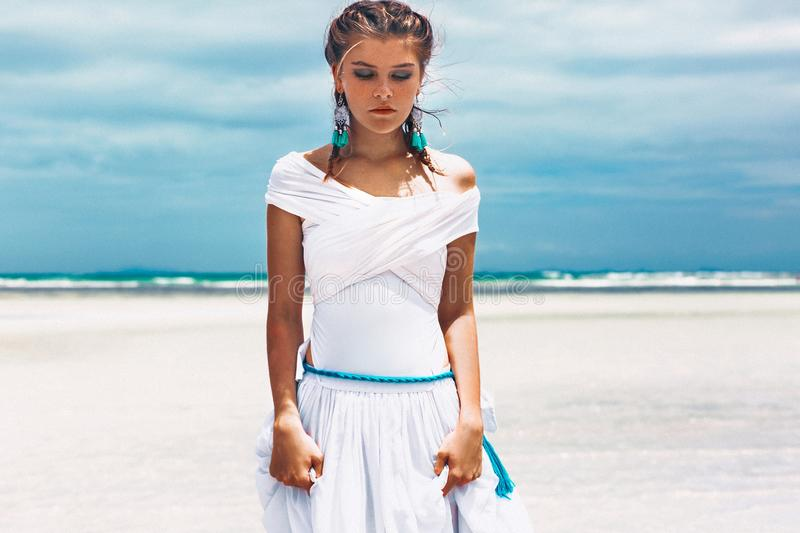Beautiful young fashionable woman in white dress at the beach. Beautiful young woman in white dress at the beach stock photo