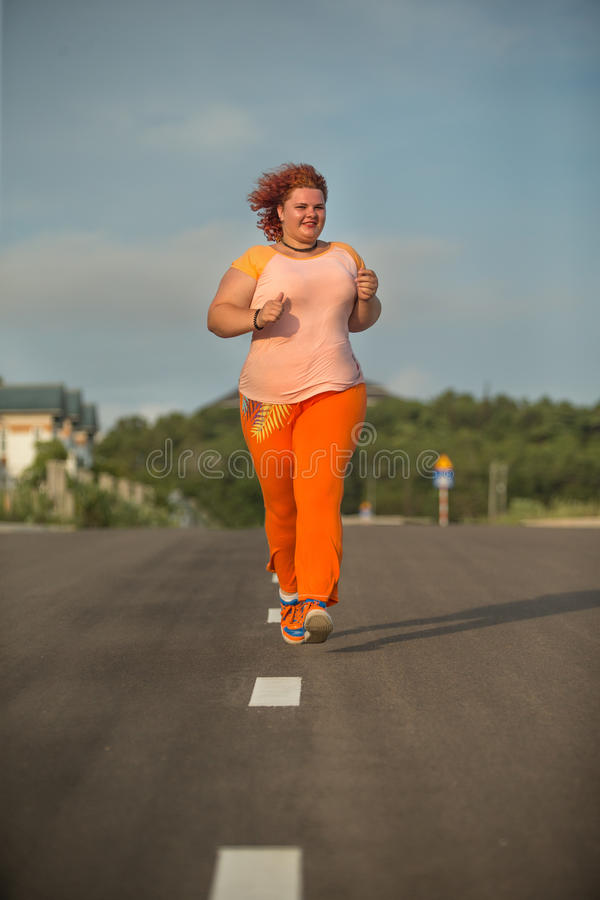 Beautiful young fat woman is runing royalty free stock photos