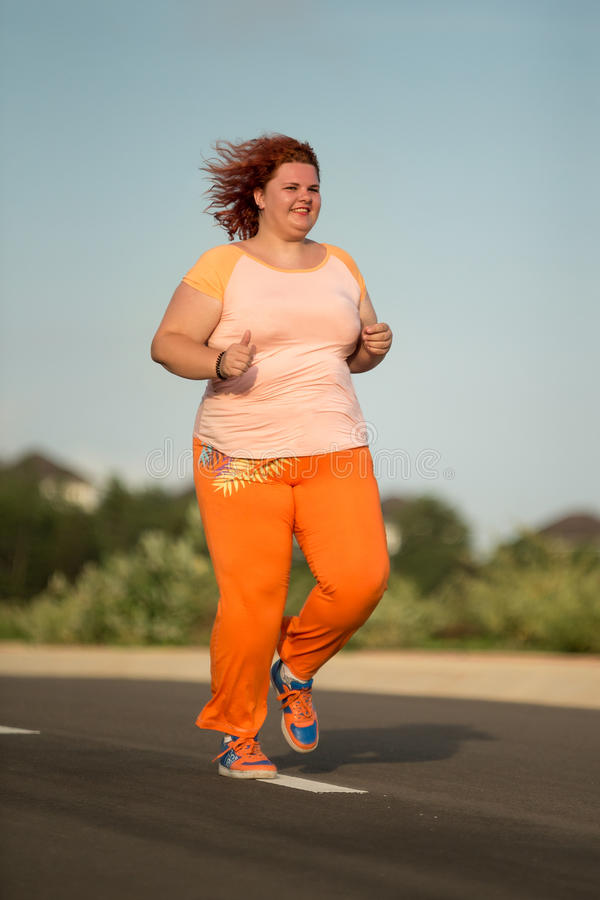 Beautiful young fat woman is runing stock image