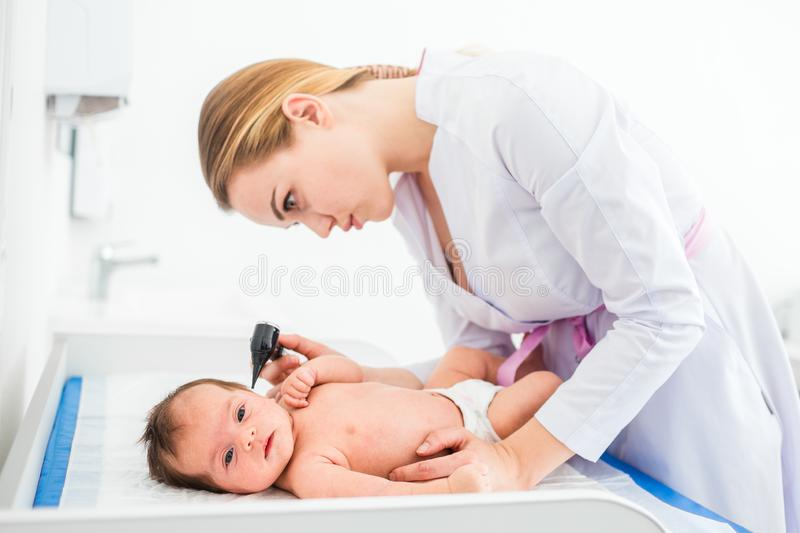 Beautiful young female blonde doctor examining little baby with ear speculum in clinic. Baby looking to the camera. Baby health stock photo