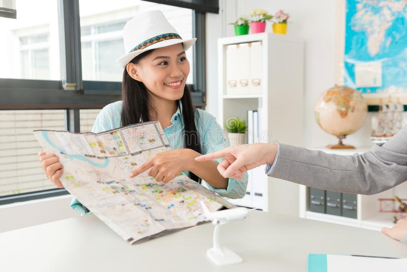 Beautiful young female customer pointing map. To ask itinerary plan when she visiting travel agent company talking with business woman royalty free stock images