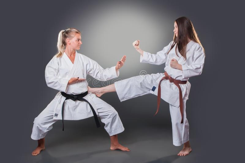 Beautiful young female karate player doing kick on the gray background royalty free stock photography