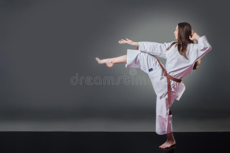 Beautiful young female karate player doing kick on the gray background royalty free stock photos
