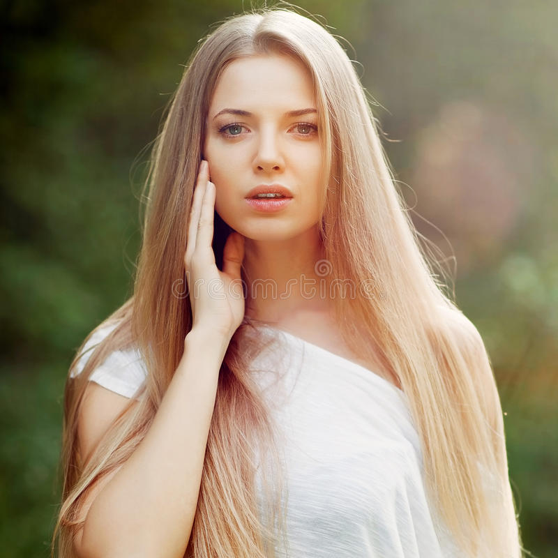 Beautiful young female model with perfect hair touching her skin stock photography