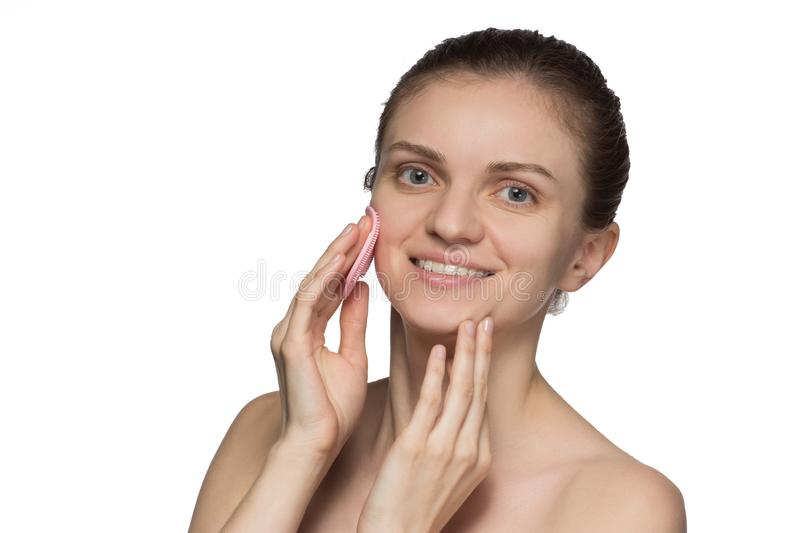 Beautiful young female model smiling and peeling face and nose w. Ith pink cosmetic silicone brush on white background royalty free stock photography