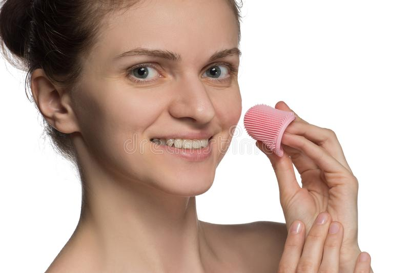 Beautiful young female model smiling and peeling face and nose w. Ith pink cosmetic silicone brush on white background stock image