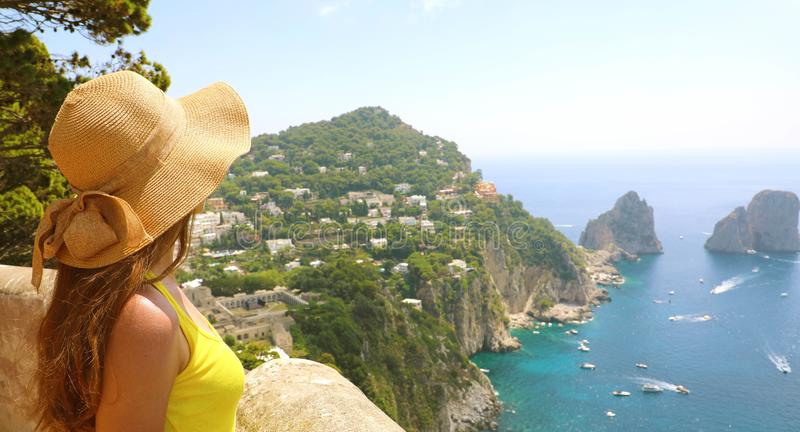 Beautiful young female model with straw hat in Capri Island with. Faraglioni sea stack and blue crystalline water on the background, Capri, Italy. Banner stock photography
