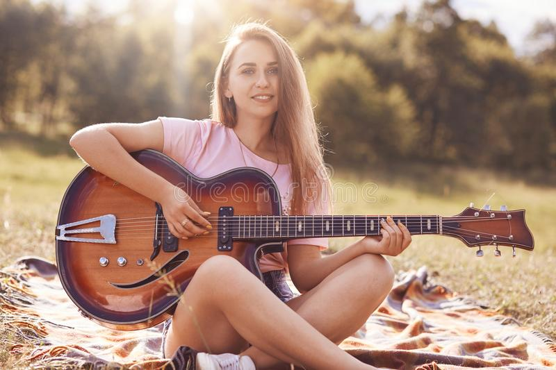 Beautiful young female musician sits crossed legs, looks with positive expression at camera, plays acoustic guitar, enjoys recreat stock photos