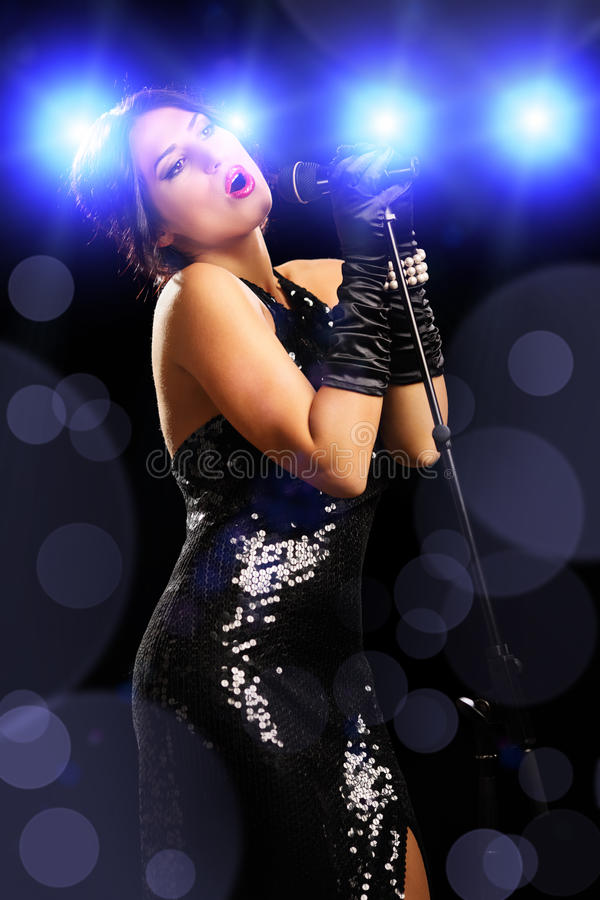 Beautiful young female singer on a rock concert and singing. Beautiful young female singer wearing black dress on a rock concert and singing royalty free stock image