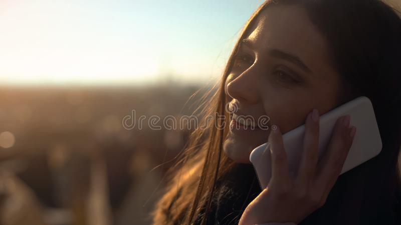 Beautiful young female talking phone on skydeck sharing impressions, roaming. Stock photo stock image