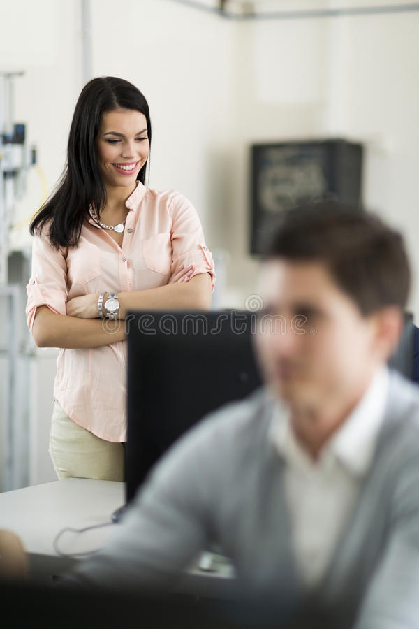 Beautiful young female teacher overseeing students' work in a cl stock image