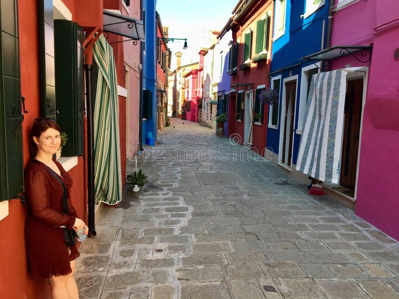 A beautiful young female tourist posing along a narrow brick road full of old colourful homes and flowers in Burano, Italy. An island outside of Venice.  The royalty free stock photos