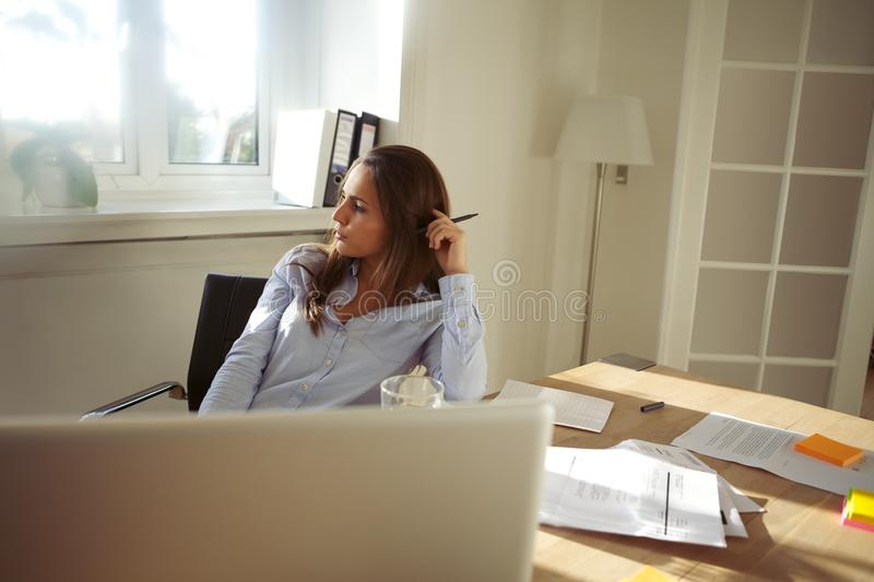Beautiful young female working at home royalty free stock images