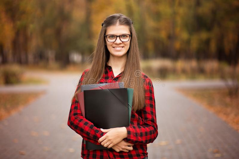 Beautiful young financial businesswoman in glasses looking at camera and smiling while standing in park royalty free stock photos