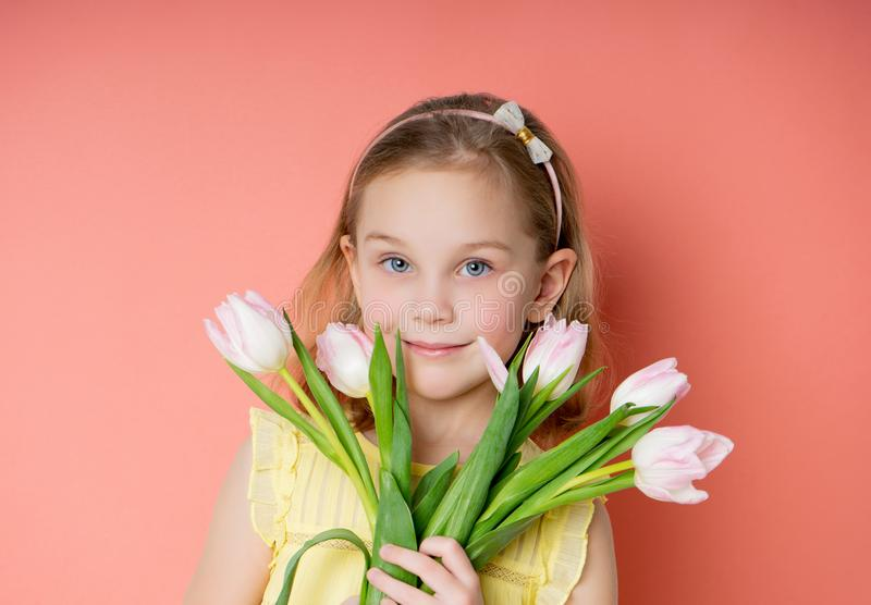Beautiful young firl in yellow dress holding spring pink flower bouquet on the pink background in the morning royalty free stock photo
