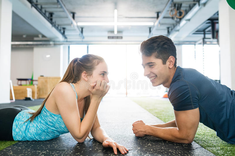 Young fit couple in gym lying on the floor, resting. Beautiful young fit couple in modern crossfit gym lying on the floor, resting stock image