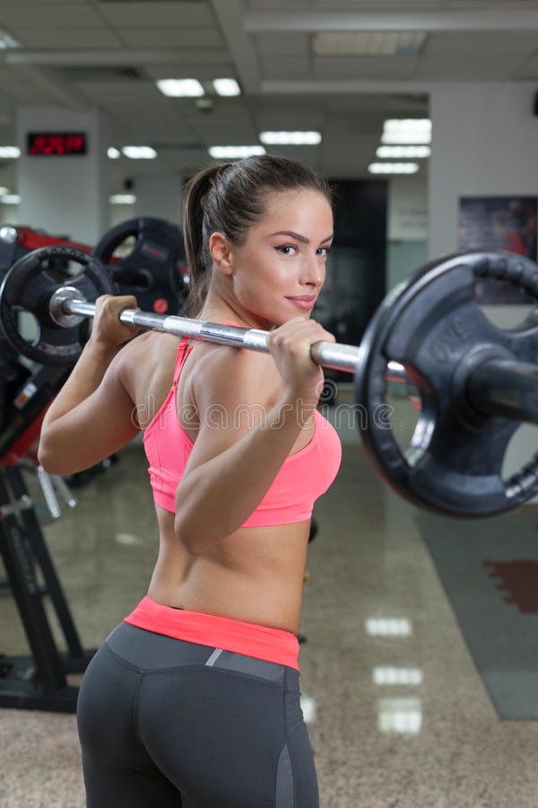 Beautiful young fit woman smiling and posing at the gym with a barbell stock photo