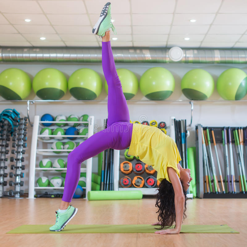 Beautiful young fit woman in sportswear doing yoga pose in gym, one-legged Upward Bow or Wheel Posture. royalty free stock photo