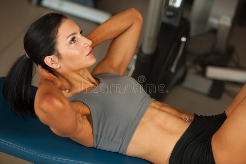 Beautiful young fit woman workout abdominal muscles abs in fitness gym stock images